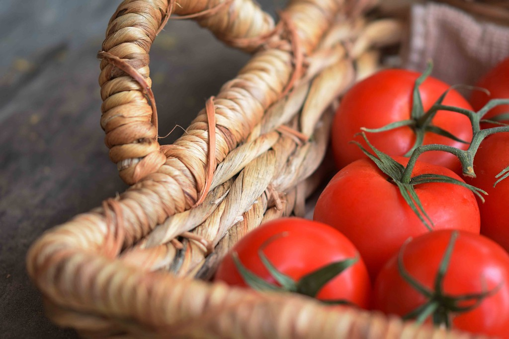 tomatoes on the vine on a basket